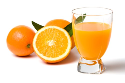 glass of orange juice in focus, oranges in background, isolated on white
