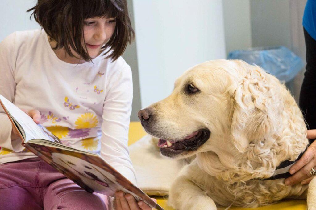 Cane che guarda un libro con una bambina