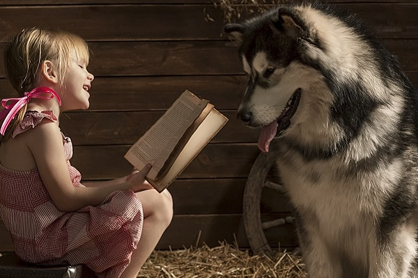 bambina legge con cane