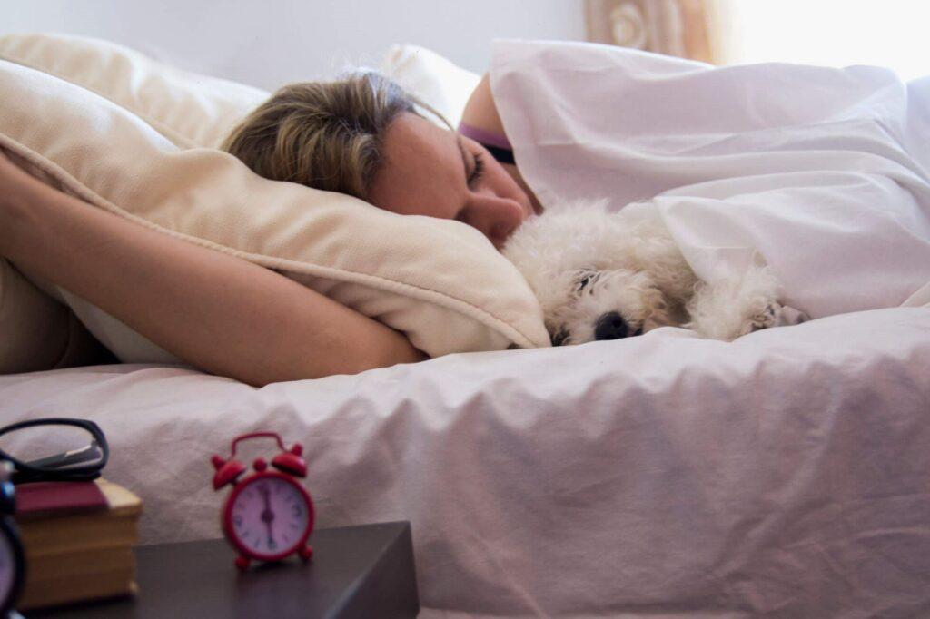 una donna dorme abbracciata al cane