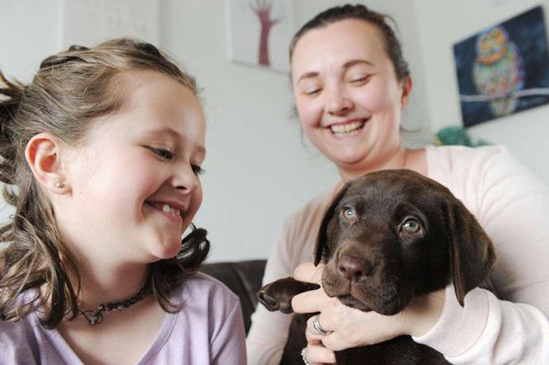 Cane insieme ad una bambina e ad una donna