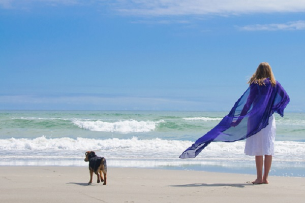 donna con cane in spiaggia