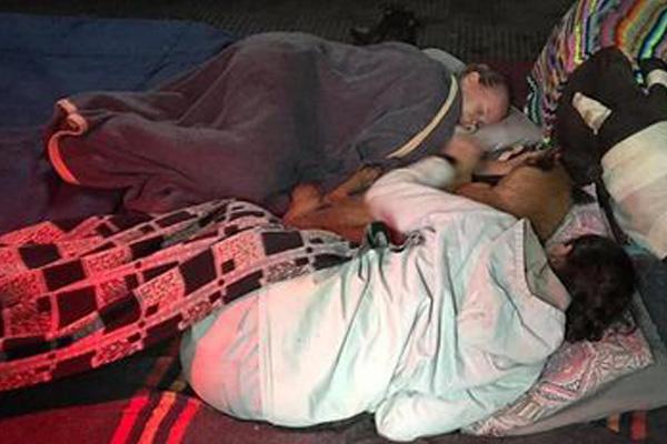 Cane che dorme con due persone