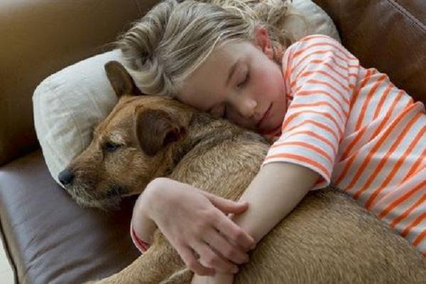 bambina dorme abbracciando un cucciolo
