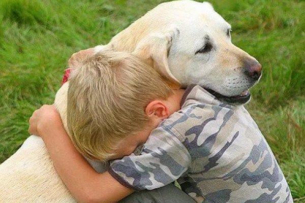 bambino biondo abbraccia cane