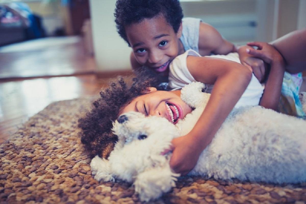 due bambini giocano con un barboncino
