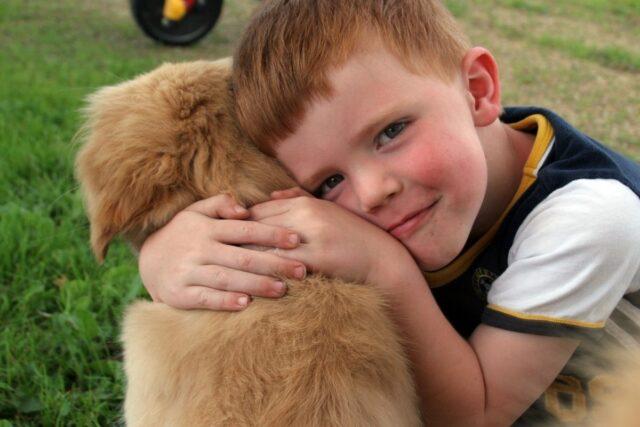 bimbo abbraccia un cucciolo