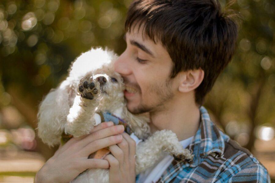ragazzo con la barba abbraccia il suo cane