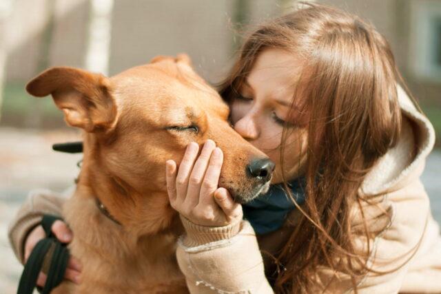 donna bacia cane sul muso