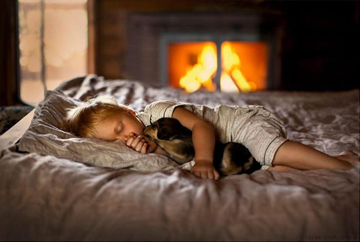 cane dorme con bambino vicino al fuoco