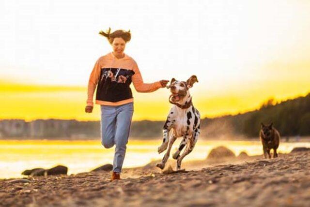 cane e padrona nella spiaggia corrono insieme