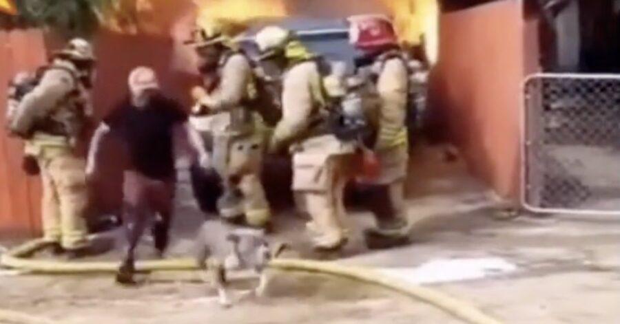 uomo esce dalla casa in fiamme con il suo cane